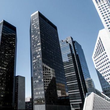 A bright and sunny downtown metropolis with tall, glass covered financial buildings.
